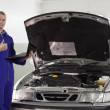 Mechanic holding a computer with thumb up - Stock Photo