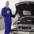 Smiling mechanic holding a computer with thumb up - Stock Photo