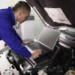 Mechanic looking at a computer on a car engine — Stockfoto