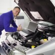 Foto Stock: Mechanic repairing car with computer
