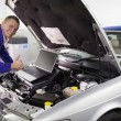 Mechanic leaning on a car engine — Stock Photo