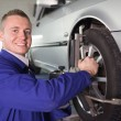 Stock Photo: Mechanic repairing a car wheel