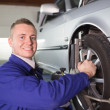 Stock Photo: Smiling mechanic repairing car wheel