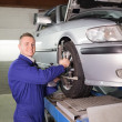 Mechanic standing while repairing a car wheel - Stok fotoğraf