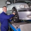 Stock Photo: Smiling mechanic standing while repairing car wheel