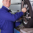 Stock Photo: Smiling mechanic changing car wheel