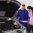 Stock Photo: Mechanic showing par of engine to woman