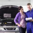 Mechanic showing a paper in a clipboard to a woman — Stock Photo