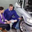 Mechanic showing the car wheel to a client — Stock Photo #14153382
