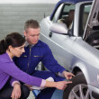 Mechanic touching the car wheel next to a woman - Stockfoto