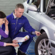 Mechanic looking at the car wheel next to a client — Stock Photo #14153388