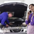 Woman calling next to a mechanic — Stock Photo