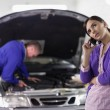 Stock Photo: Client calling next to mechanic
