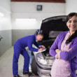 Woman smiling with arms crossed next to a mechanic — Foto Stock