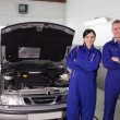 Foto Stock: Mechanics next to car