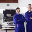 Stock Photo: Smiling mechanics with arms crossed