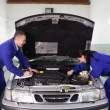 Mechanics examining a car engine — Stockfoto