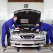 Stock Photo: Mechanics looking at engine