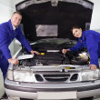 Stock Photo: Mechanics leaning on car