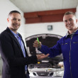 Mechanic smiling while giving car key to a man — Stock Photo