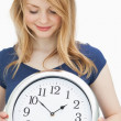 Blonde woman holding a clock while smiling — Stock Photo