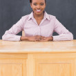 Teacher smiling while sitting at her desk — Stock Photo #14155387