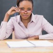 Teacher sitting at desk while touching her glasses — Stock Photo #14155583