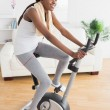 Black woman doing exercise bike while smiling - Stock Photo