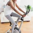 Black woman doing exercise bike with headphones — Foto Stock