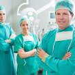Surgical team smiling with arms crossed - Stock Photo