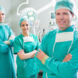 Surgical team with arms crossed smiling - Stock Photo