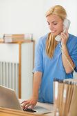 Blonde nurse calling while using a laptop — Stock Photo