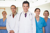 Doctors with nurses looking at camera — Stock Photo