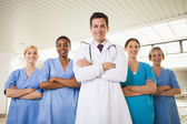 Smiling doctor and nurses with arms crossed — Stock Photo