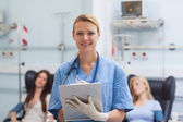 Nurse writing on a clipboard next to patients — Stock Photo