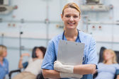Smiling nurse holding a clipboard — Stock Photo