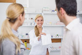 Pharmacist giving a drug bag to patients — Stock Photo