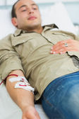 Male transfused lying on a bed — Stock Photo