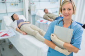Nurse standing next to transfused patients — Stock Photo