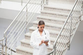 Doctor using a tablet computer on stairs — Stock Photo