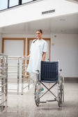 Smiling patient standing next to a wheelchair — Stock Photo