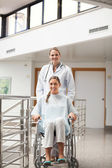 Patient sitting on a wheelchair next to a doctor — Stock Photo