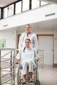Paciente sentado em uma cadeira de rodas ao lado de um médico — Foto Stock