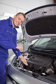 Smiling mechanic showing an engine — Stock Photo