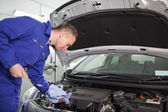Mechanic looking at a dipstick while holding it — Foto de Stock