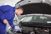 Mekaniker tittar på en mätsticka medan du håller det — Stockfoto