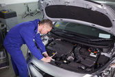 Concentrated mechanic repairing a car — Stock Photo