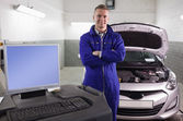 Mechanic next to a car and a computer — Stock Photo