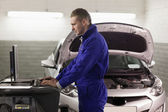 Concentrated mechanic looking at a computer — Stock Photo