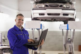 Mechanic typing on a laptop — Stock Photo